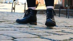 Fin vers le haut des pieds des femmes dans les bottes noires sur le trottoir de pavé rond clips vidéos