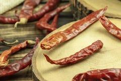 Fin vers le haut des piments rouges secs sur le fond en bois de table photos stock