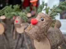 Fin vers le haut des versions en bois de rondin de temps flairé rouge de vacances de Noël de renne de Rudolph photographie stock libre de droits