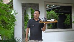 Fin vers le haut du serveur asiatique de sourire tenant le plateau en bois avec la théière, visiteur servant clips vidéos