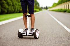 Fin vers le haut Jambes du ` s d'hommes dans des espadrilles sur le gyroboard Un homme monte sur une route en parc de pays Image libre de droits