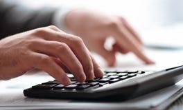 Fin vers le haut l'homme d'affaires effectue des calculs sur la calculatrice photographie stock