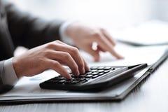 Fin vers le haut l'homme d'affaires peut utiliser la calculatrice pour calculer le b?n?fice photographie stock libre de droits