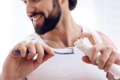 Fin vers le haut L'homme de sourire barbu serre la pâte dentifrice sur la brosse à dents photos stock