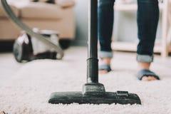 Fin vers le haut La femme nettoie le tapis avec l'aspirateur images libres de droits