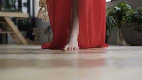 Fin vers le haut La fille dans la robe rouge va nu-pieds sur le plancher sur l'appareil-photo banque de vidéos