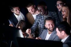 Fin vers le haut Les hommes d'affaires gais regardent l'écran d'ordinateur photo libre de droits