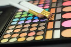 Fin vers le haut mensonge de brosses de maquillage sur l'ensemble de cosmétique photos stock