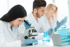 Fin vers le haut le scientifique féminin utilise un microscope pour analyser le liquide photos stock