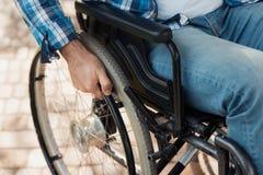 Fin vers le haut Un homme handicapé dans un fauteuil roulant tient des mains derrière les roues de fauteuil roulant Photographie stock libre de droits