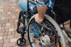 Fin vers le haut Un homme handicapé dans un fauteuil roulant tient des mains derrière les roues de fauteuil roulant Photo libre de droits