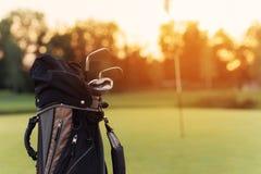 Fin vers le haut Un sac pour des clubs de golf avec des clubs de golf sur le fond de coucher du soleil Photo stock