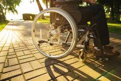 Fin vers le haut Un vieil homme s'assied sur un fauteuil roulant en parc Photo libre de droits