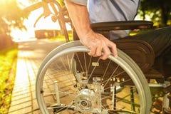 Fin vers le haut Un vieil homme s'assied sur un fauteuil roulant en parc Image libre de droits