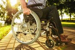 Fin vers le haut Un vieil homme s'assied sur un fauteuil roulant en parc Images libres de droits