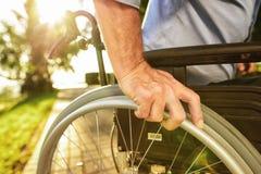 Fin vers le haut Un vieil homme s'assied sur un fauteuil roulant en parc Image stock