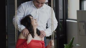 Fin vers le haut Une femme enceinte dans une robe rouge s'assied sur l'oscillation, et ses supports de mari derrière ses étreinte clips vidéos