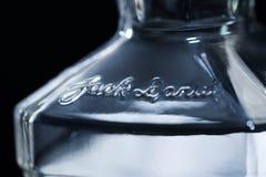 Fin vide de bouteille de Jack Daniels vers le haut du macro tir d'isolement sur le fond noir image stock