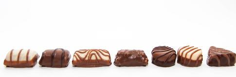 Fina bruna vita chokladbrända mandlar på en enkel rad Royaltyfri Fotografi