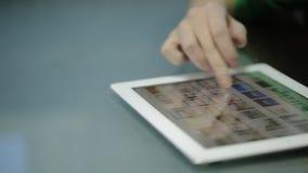Fina fingrar för ung kvinna glider på skärmminnestavladatoren, som ligger på en glansig tabell lager videofilmer