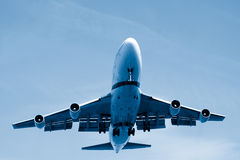 Final Approach. Airliner on final approach, landing gear down, landing lights on. Blue toned image Stock Photos
