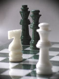 Final attack. Two white chess marble pieces attacking two black/green marble chess Royalty Free Stock Photography
