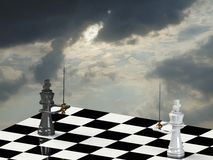 The final battle. Chess board with King pieces face to face and a cloudy background Royalty Free Stock Photos
