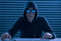 Serious male gamer involving in online game. Final battle. Confident ambitious male gamer sitting at the table while dressing in hood and wearing glasses Stock Image