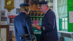 Final checking before the arrival of the train. Slow motion RAW footage of a conductor and a woman  working at the train station museum in the countryside stock video footage
