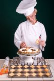 Final Chef Touches. Passive posed uniformed smiling female Pastry Chef adding final touch to large pumpkin pie Royalty Free Stock Photos
