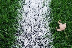 Final de la estación de fútbol Hoja seca en la tierra del césped verde plástico del fútbol con la línea blanca pintada Imagenes de archivo
