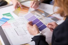 FInal decisions concerning their new house's design. Close-up of technical drawings and colour samplers with a group of people choosing between them Stock Photo