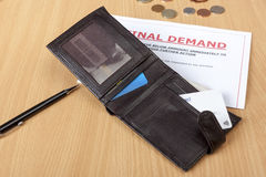 Final demand letter on a desk with a wallet. Final demand on a desk with a credit card in a wallet with some cash Stock Images