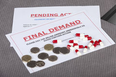 Final demands on a table with cash and pills Stock Photography