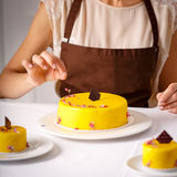 Final embellishment of big yellow cake. Final embellishment of big yellow cake by fall flower petal Royalty Free Stock Photo