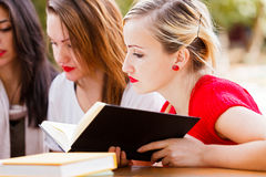 Final Exmaniation. Girl friends outdoors preparing for studying for the final examination stock photos