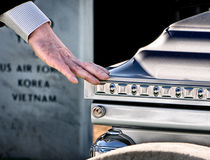 Final Farewell. Military funeral at Arlington National Cemetery with mourner touching casket in gesture of farewell Stock Image