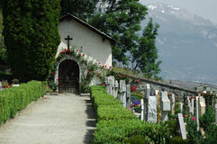 The Final Journey. Path leading to the mortuary in a swiss village cemetry.  On either side of the path gravestones of the deceased.  In the background residual Stock Photography