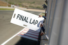 Final Lap. Man, holding out a notice board, informing their race car driver of the Final Lap, through the fences surrounding the pit lane along the final Stock Image