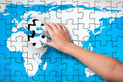 Final Piece. Child's hand, inserting missing piece of jigsaw puzzle world map into the hole. Photomontage, compiled from photography and 3D-rendered image stock image