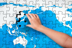 Final Piece. Child's hand, inserting missing piece of jigsaw puzzle into the world map hole. Photomontage, compiled from photography and 3D-rendered image Royalty Free Stock Photos