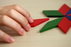 Final Piece. Child's hand. Inserting missing piece of blank puzzle into the hole stock photo