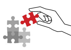 Final piece of puzzle. Hand holding red piece of puzzle over grey unfinished pieces Stock Image