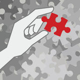 Final piece of puzzle. Hand holding red piece of puzzle over grey unfinished pieces Royalty Free Stock Images