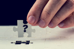 Final puzzle piece with a question mark. Man holding the final puzzle piece with a question mark hand-drawn on it in his fingers above a jigsaw puzzle conceptual Stock Image