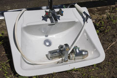 Final rest of a bathroom sink. An old bathroom sink and shower mixer lies on the ground after being replaced with modern variants Royalty Free Stock Photography