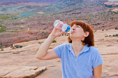 Final sip of water in a bottle. Woman hiker at mountain valley. Stock Images