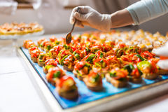 Final touch for tasty canapes. Chef is using gloves for adding the final dressing on delicious canapes stock photography