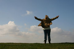 Finally. Girl raising arms on hilltop Stock Image