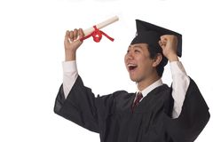 Finally. Young asian graduate holding his diploma and cheering Royalty Free Stock Image